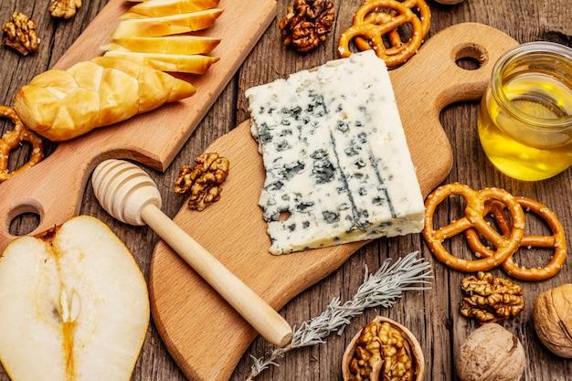Kaasplaatantipasti met gerookte en blauwe kaas, crackers, honing, walnoten en rijpe peer. traditioneel snackrecept