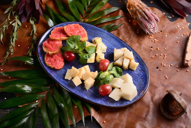 Kaasplakken met druiven in een blauwe plaat. met bloemendecor