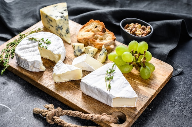 Kaasplank met franse camembert, brie en blauwe kaas, druiven en walnoten. zwarte achtergrond. bovenaanzicht