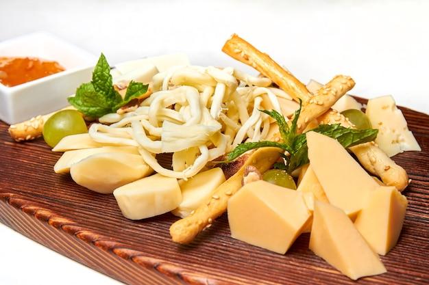 Kaasplankje met feta parmezaanse mozzarella kaasstengels gevlochten kaas met honing