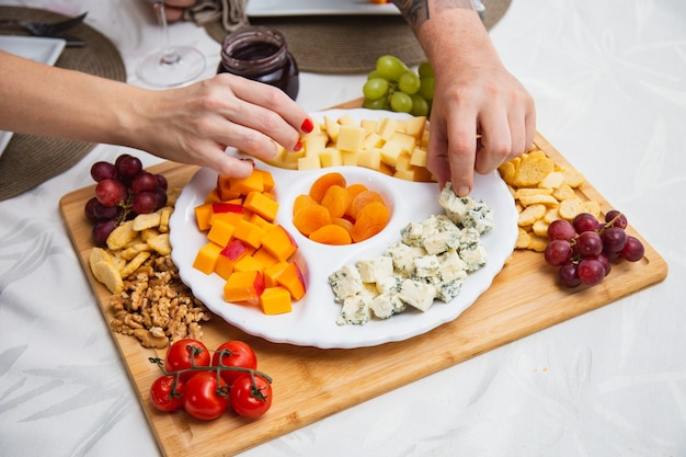 Kaasplankje met verschillende hapjes op tafel. aardbeien-, abrikozen-, druiven- en graankaasschotels op tafel