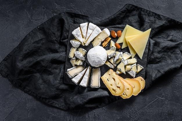 Kaasplateau geserveerd met noten en vijgen. frans voorgerecht. zwarte achtergrond. bovenaanzicht