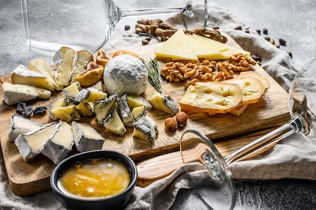 Kaasplateau geserveerd met noten en vijgen. italiaanse antipasto. grijze achtergrond. bovenaanzicht