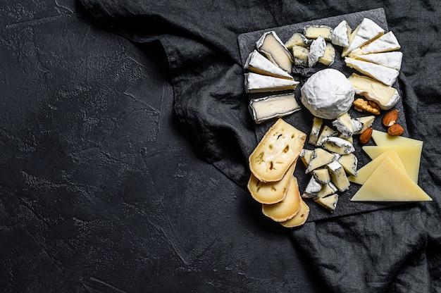 Kaasplateau geserveerd met noten en vijgen. zwarte achtergrond. bovenaanzicht