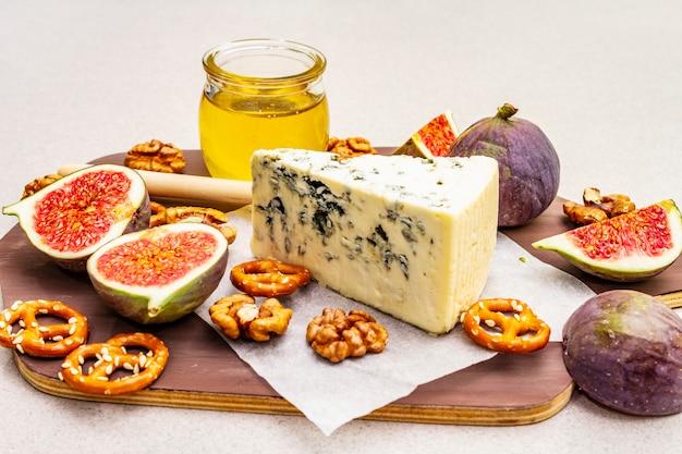 Kaasschotel (bord) met blauwe kaas, honing, walnoten, vijgen, pretzels