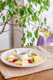 Kaasschotel. een bord met diverse kazen. snacks. glas wijn met kaas.