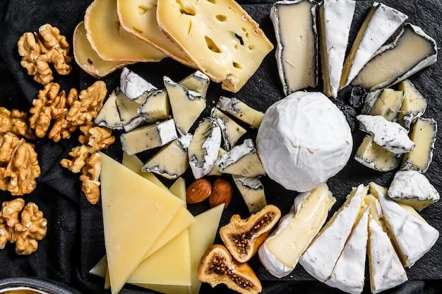 Kaasschotel met biologische kazen, vijgen, noten op zwarte achtergrond. bovenaanzicht lekkere kaas voorgerecht