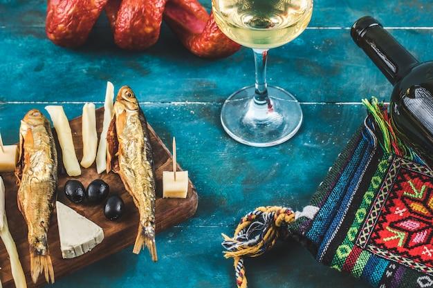 Kaasstokken met gerookte vis op blauwe achtergrond met een glas wijn