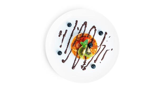 Kaastaart met chocolade en fruit op wit wordt geïsoleerd.