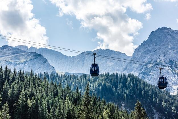Kabelbaan en skiërs op de helling van de berg