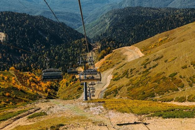 Kabelbaan hoog in de bergen boven de herfst bos