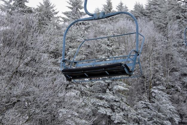 Kabelbaan met besneeuwde bomen op de achtergrond