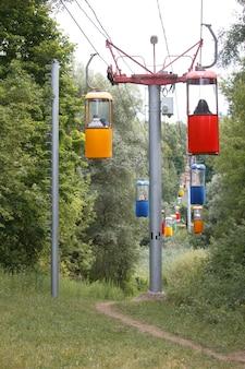 Kabelbaan van kleurrijke cabines op de achtergrond van een dicht groen park