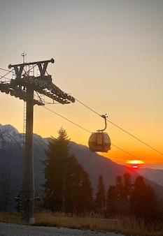 Kabelbaangondel in de bergen bij zonsondergang