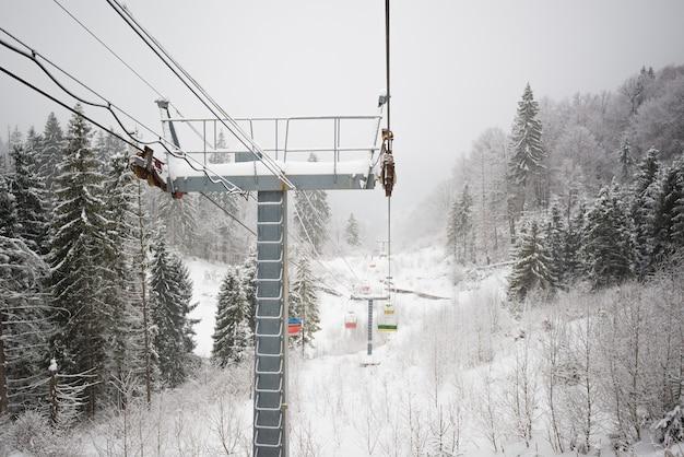 Kabelbanen bevinden zich tussen heuvelachtige bergen en bomen die in ijzige winterse tijden met sneeuw bedekt zijn.