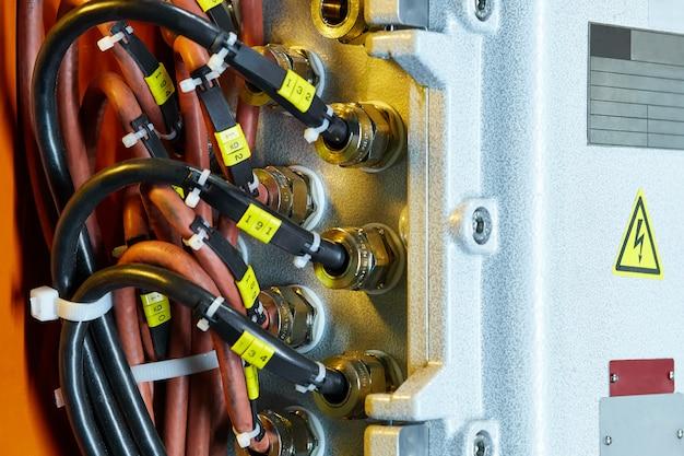 Kabelclose-up verbonden met het schakelbord met behulp van moeren, op de schakelbordplaten om de informatie in te vullen