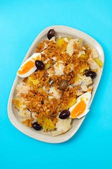 Kabeljauw met zoete aardappel, gekookt ei, olijven en maisbrood op witte schotel