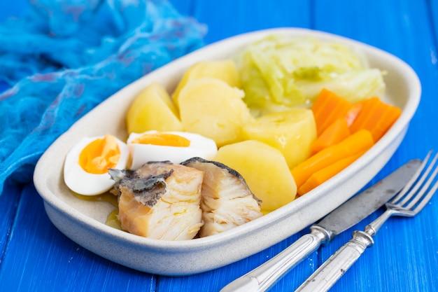 Kabeljauw vis met gekookt ei en groenten op schotel