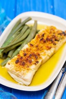 Kabeljauwvissen met maïsbrood en slabonen op schotel