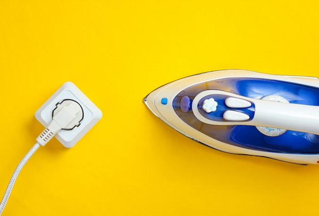 Kabelstrijkijzer voor het strijken van dingen die op een stopcontact in een gele tafel zijn aangesloten. bovenaanzicht, minimalisme