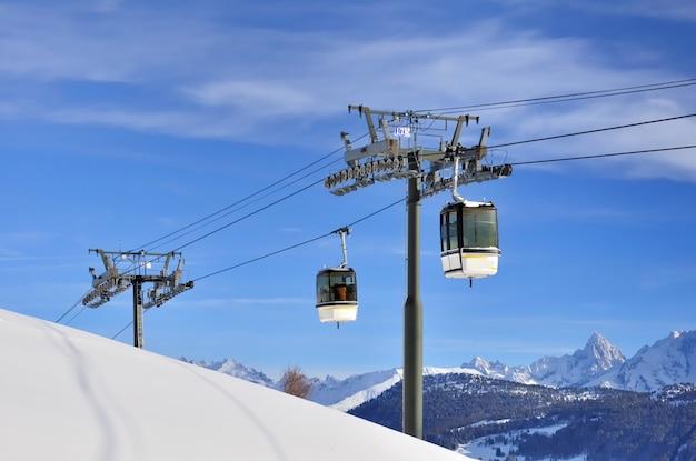 Kabelwagen tegen blauwe hemel boven piek sneeuwberg