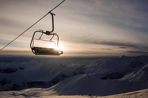 Kabelwagencabine het hangen op hoge bergpieken en hemel met glanzende hemel