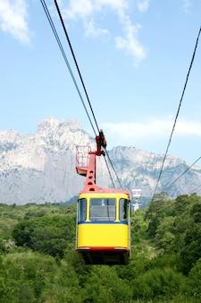 Kabelwagencabine op een bergachtergrond. de opkomst van de kabelbaan naar de bergen in de zomer