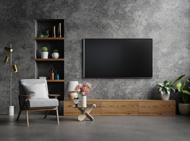 Kabinet-tv in moderne woonkamer met fauteuil, lamp, tafel, bloem en plant op betonnen muur