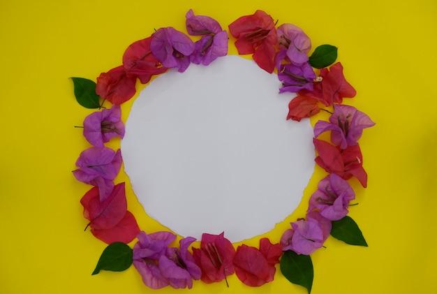 Kader dat van verse kleurrijke bloemen met witte ruimte voor tekst op gele achtergrond wordt gemaakt.
