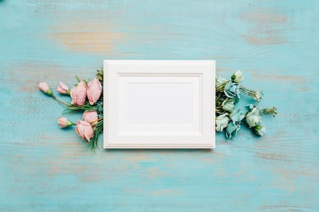 Kader en bloemen op blauwe houten achtergrond. Gratis Foto