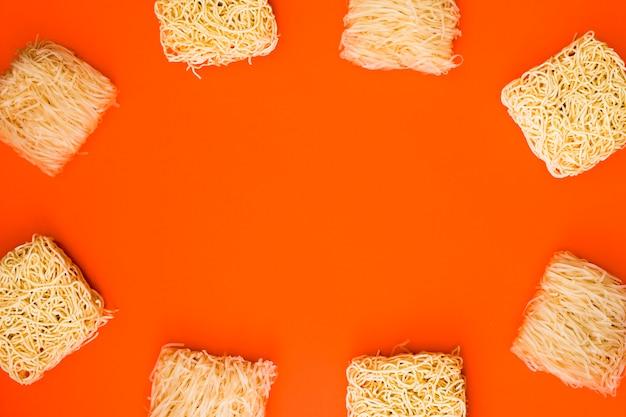 Kader met verscheidenheid van ruwe noedelblokken wordt gemaakt over oranje achtergrond die
