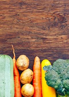 Kader van groentenstilleven op houten achtergrond met exemplaarruimte