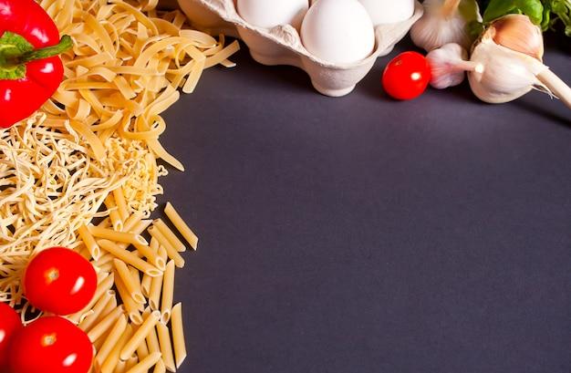 Kader van macaroni en groenten op de zwarte achtergrond. ruimte kopiëren. bovenaanzicht.