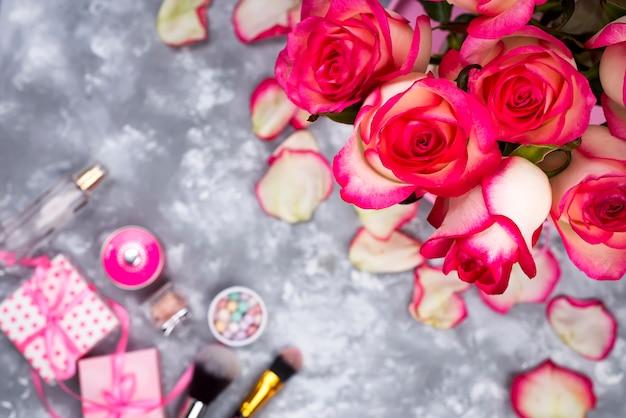 Kader van mooie rozen met schoonheidsmiddelen op grijs beton
