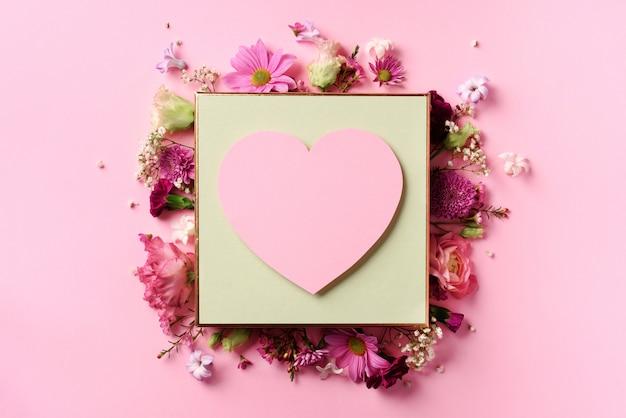 Kader van roze bloemen over punchy pastelkleurachtergrond.