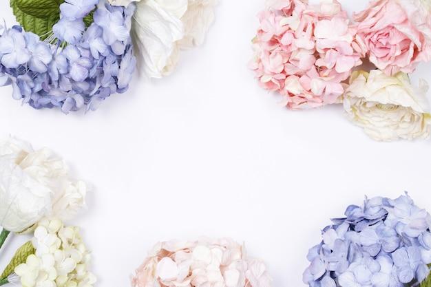 Kader van roze en beige rozen op witte achtergrond wordt gemaakt die.