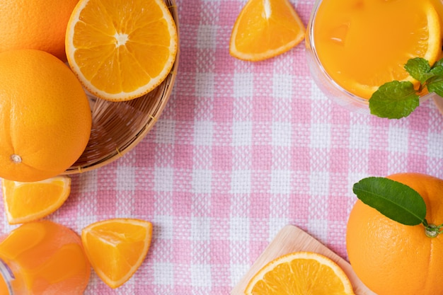 Kader voor tekst met gesneden oranje fruit op de roze achtergrond van de tafelkleedtextuur, mening van bovengenoemde lijst.