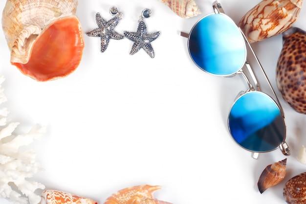 Kadergrens met copyspace van blauwe zonnebril verschillende zeeschelpen van overzeese weekdieren en zeesteroorringen op wit.