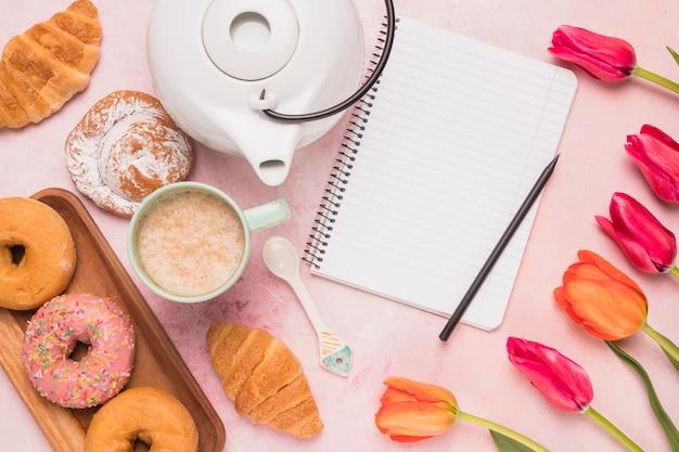 Kadernotitieboekje met zoete koffiepauze en tulpen