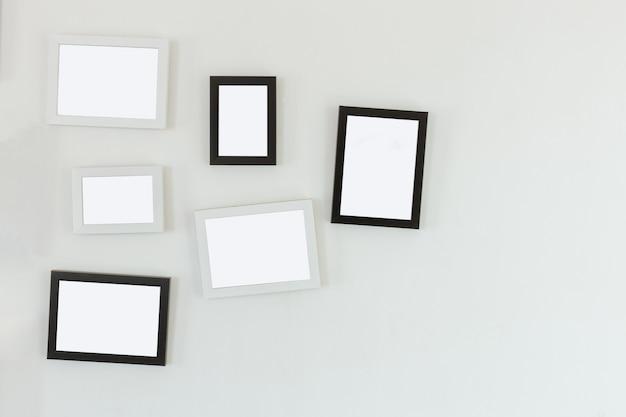 Kaders die op witte muur hangen