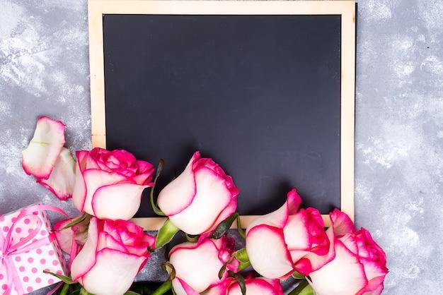 Kadersamenstelling met rozen en giftdoos op steenachtergrond.
