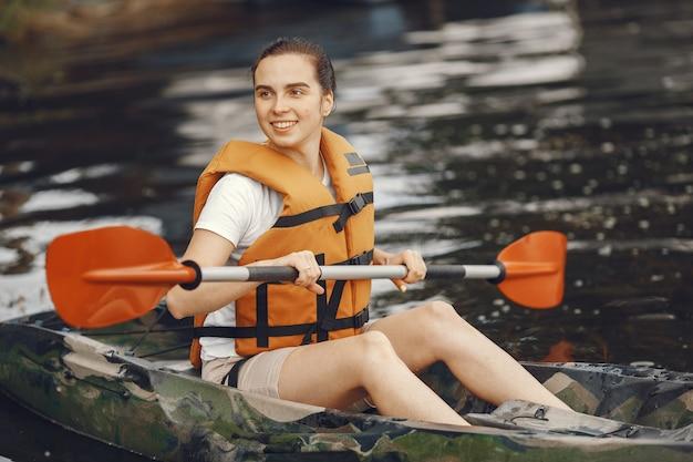 Kajakken. een vrouw in een kajak. meisje peddelen in het water.