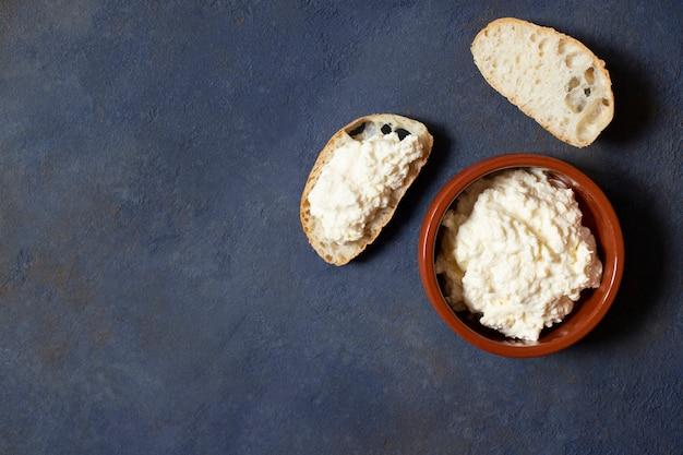 Kajmak of kaymak. traditionele huisgemaakte witte kaas. sandwich met kajmak. balkan-keuken. servische keuken. donkere achtergrond. bovenaanzicht. ruimte voor tekst