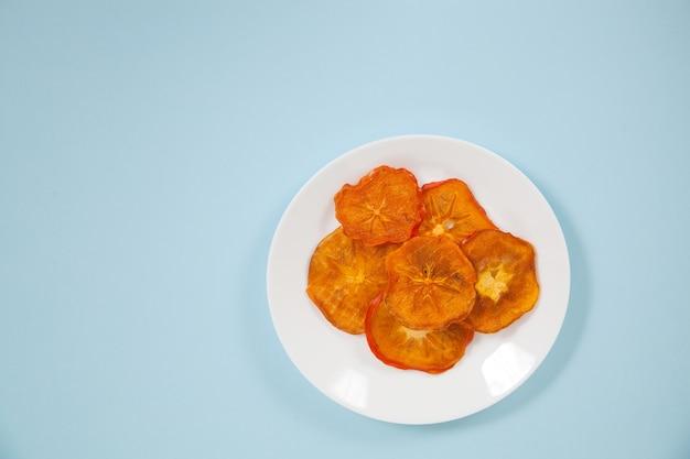Kaki chips liggen op een porseleinen bord