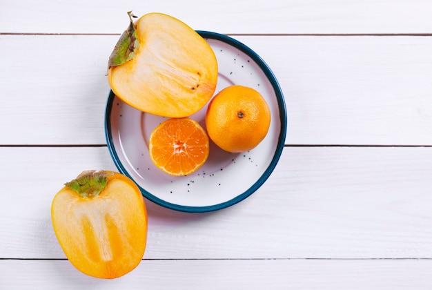 Kaki en sinaasappel op bord