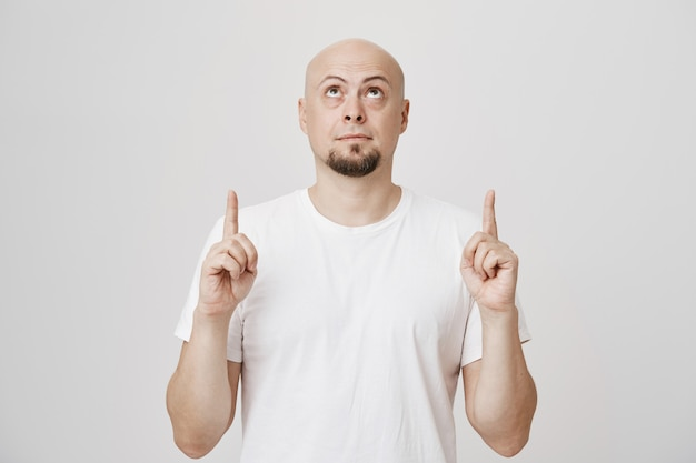 Kale bebaarde man van middelbare leeftijd in wit t-shirt kijken en naar copyspace benadrukken