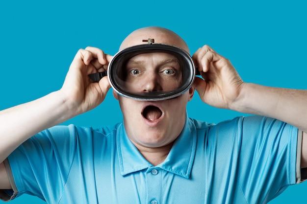 Kale brutale man in een duikbril houdt zijn adem in op blauw