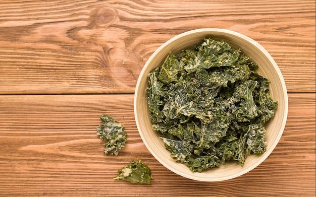 Kale chips op een houten tafel. kopieer ruimte
