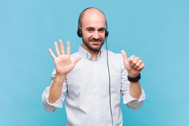 Kale en mens die vriendelijk glimlacht kijkt, nummer zes of zesde met vooruit hand toont, aftellend