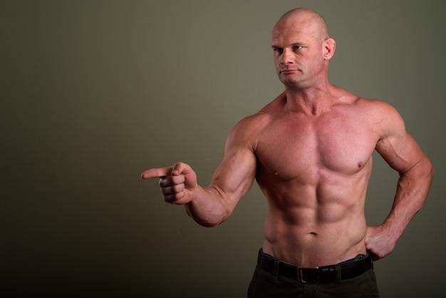 Kale gespierde man shirtless tegen gekleurde muur